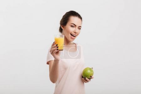 Photo pour Belle fille clin d'oeil et tenant verre de jus et de pomme isolé sur blanc - image libre de droit