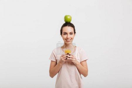 Photo pour Belle fille avec apple sur la tête en tenant le verre de jus isolé sur blanc - image libre de droit
