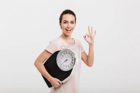beautiful girl holding scales and showing ok gesture isolated on white