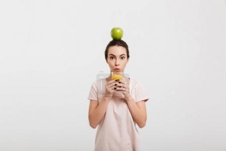 Photo pour Fille avec apple sur la tête en tenant le verre de jus isolé sur blanc - image libre de droit