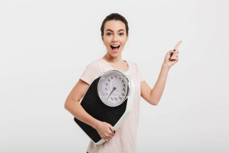 happy girl holding scales and pointing on something isolated on white