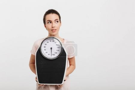 Photo for Beautiful girl holding scales and looking away isolated on white - Royalty Free Image