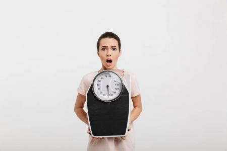 Photo for Shocked young woman holding scales isolated on white - Royalty Free Image
