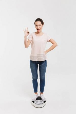young woman showing okay sign while standing on scales isolated on white