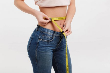 Photo for Cropped shot of woman measuring her waist isolated on white - Royalty Free Image