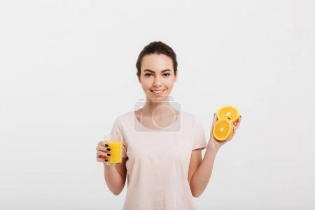 Photo pour Belle jeune femme avec des jus de fruits frais et les moitiés d'orange isolé sur blanc - image libre de droit