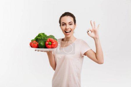 Photo pour Jeune femme avec plateau de divers légumes frais montrer signe OK isolé sur blanc - image libre de droit