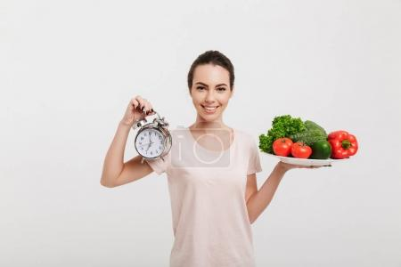 Photo for Young woman with tray of various fresh vegetables and alarm clock isolated on white - Royalty Free Image