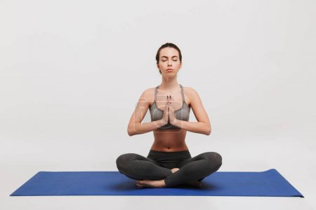 Photo for Young woman meditating in lotus pose on yoga mat isolated on white - Royalty Free Image