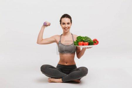 Photo pour Heureuse jeune femme assise sur le sol avec plateau de divers légumes sains et montrant ses muscles isolés sur blanc - image libre de droit