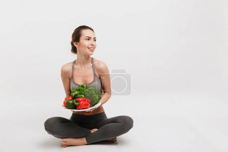 Photo for Happy young woman sitting on floor with tray of various healthy vegetables isolated on white - Royalty Free Image
