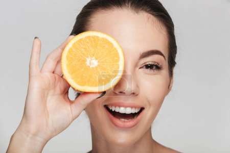 Photo for Young woman covering one eye with half of orange isolated on white - Royalty Free Image