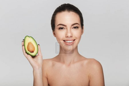 Photo for Attractive young woman with half of fresh avocado isolated on white - Royalty Free Image