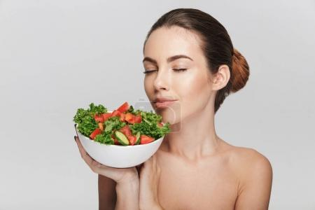 Photo for Attractive young woman with bowl of healthy salad isolated on white - Royalty Free Image