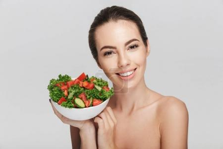 Photo for Beautiful young woman with bowl of healthy salad isolated on white - Royalty Free Image
