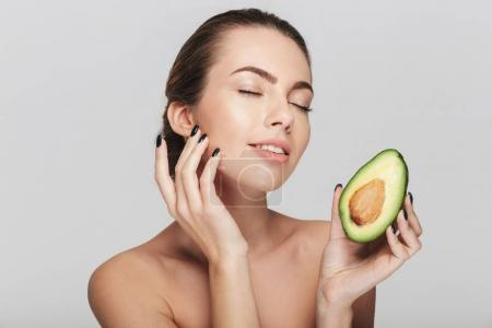 Photo for Young woman with perfect skin holding half of fresh avocado isolated on white - Royalty Free Image