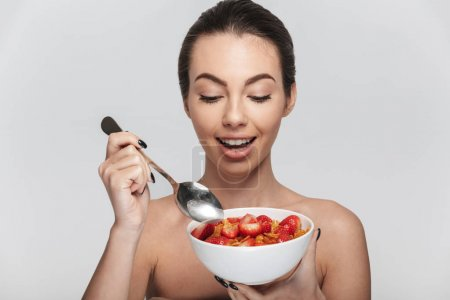 Photo for Happy young woman eating cereal breakfast with strawberries isolated on white - Royalty Free Image