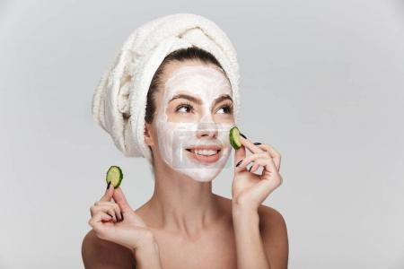 Photo for Young woman with facial skincare mask and cucumber slices isolated on white - Royalty Free Image