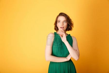 Photo for Portrait of young pensive woman looking away isolated on orange - Royalty Free Image