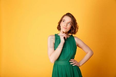 Photo pour Portrait de jeune femme réfléchie en levant isolés sur orange - image libre de droit