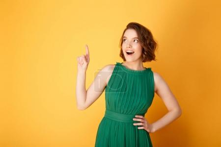 Photo for Portrait of young emotional woman pointing up isolated on orange - Royalty Free Image