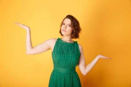 Photo for Portrait of young pensive woman gesturing isolated on orange - Royalty Free Image