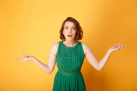 Photo for Portrait of young shocked woman with outstretched arms isolated on orange - Royalty Free Image