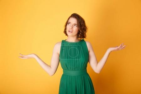 portrait of confused woman with outstretched arms isolated on orange