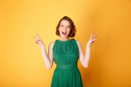 Photo for Portrait of young happy winking woman showing peace sign isolated on orange - Royalty Free Image