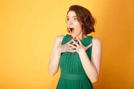 portrait of young shocked woman looking away isolated on orange