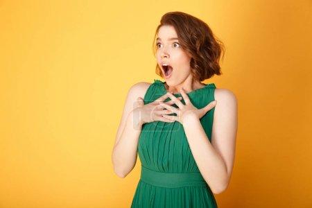 retrato de mujer joven sorprendida mirando hacia otro lado aislado en naranja