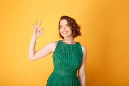 Photo for Portrait of pretty smiling woman showing ok sign isolated on orange - Royalty Free Image