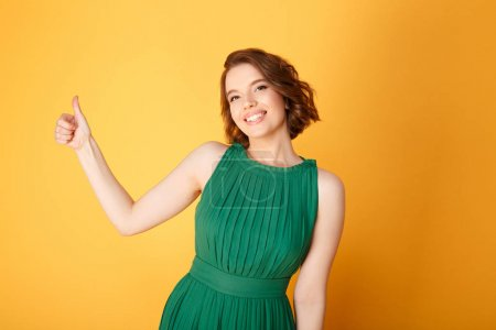 portrait of pretty smiling woman showing thumb up isolated on orange