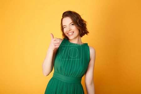 Photo for Portrait of cheerful woman pointing at camera isolated on orange - Royalty Free Image
