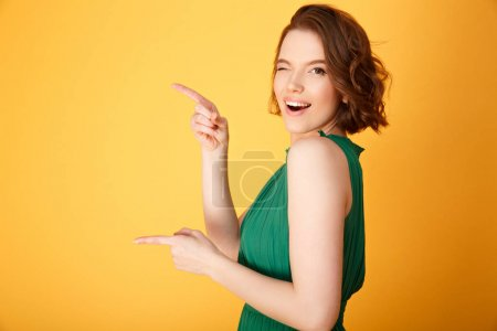 Photo for Side view of attractive winking woman pointing away isolated on orange - Royalty Free Image