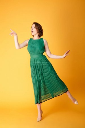 Photo for Beautiful surprised woman in green dress pointing away isolated on orange - Royalty Free Image