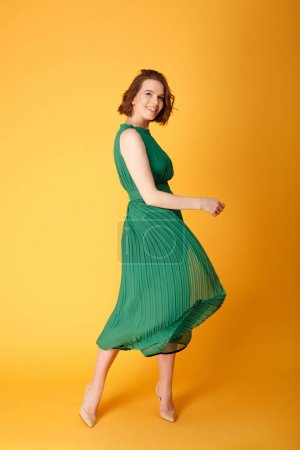 Photo for Young beautiful woman in green dress dancing isolated on orange - Royalty Free Image