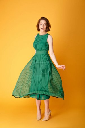 Photo pour Belle jeune femme en robe verte, isolée sur orange - image libre de droit