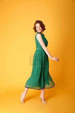 Photo pour Jeune femme joyeuse en robe verte, isolée sur orange - image libre de droit