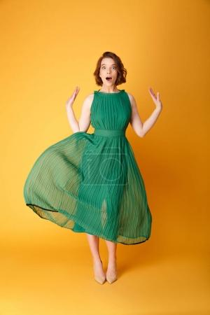 Photo for Surprised beautiful woman in green dress isolated on orange - Royalty Free Image