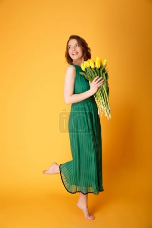 cheerful woman in green dress with bouquet of yellow tulips isolated on orange