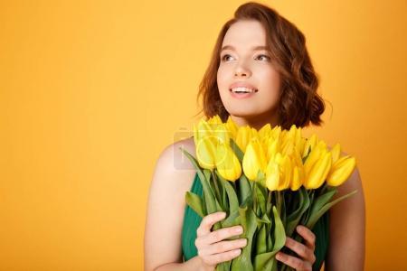 Photo pour Portrait de femme heureuse avec bouquet de Tulipes jaunes isolées sur orange - image libre de droit