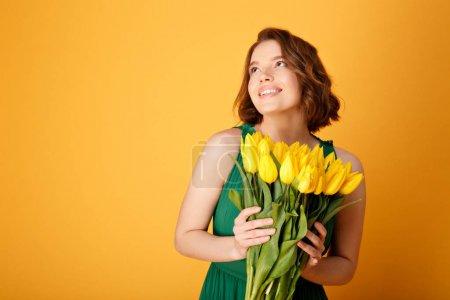 Photo pour Femme de rêve de pf portrait avec bouquet de Tulipes jaunes isolées sur orange - image libre de droit