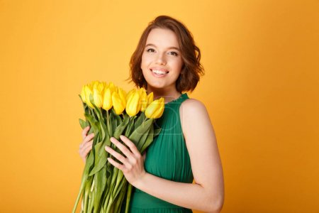 Photo pour Portrait de femme joyeuse en robe verte avec bouquet de Tulipes jaunes isolées sur orange - image libre de droit