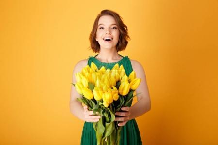Photo pour Heureuse jeune femme tenant bouquet de tulipes jaunes dans les mains isolées sur orange - image libre de droit