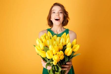 Photo for Selective focus of happy woman presenting bouquet of yellow spring tulips in hands isolated on orange - Royalty Free Image