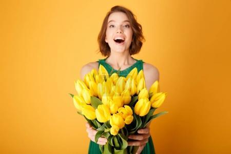 Foto de Enfoque selectivo de mujer feliz que presenta ramo de tulipanes amarillo primavera en manos aisladas en naranja - Imagen libre de derechos