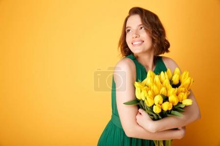 Photo pour Portrait de femme souriante étreindre bouquet de Tulipes jaunes isolées sur orange - image libre de droit