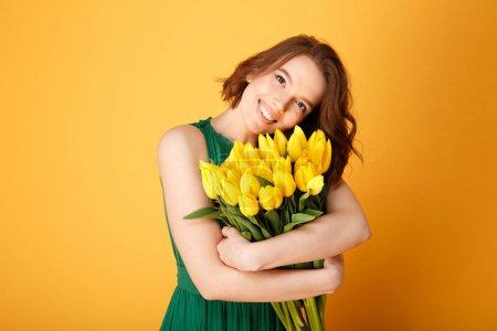 Photo pour Souriante jeune femme au bouquet de Tulipes jaunes printemps regardant caméra isolée sur orange - image libre de droit