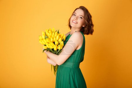 Photo for Side view of beautiful woman with bouquet of yellow tulips looking at camera isolated on orange - Royalty Free Image